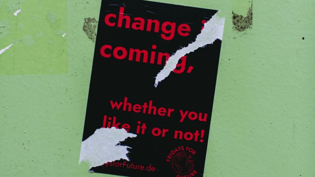 Schwarzes Plakat mit rotem Schriftzug Change is coming, wether you like it or not
